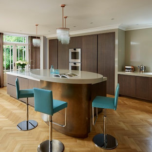 Contemporary kitchen in London with flat-panel cabinets, dark wood cabinets, granite worktops, integrated appliances, medium hardwood flooring, an island, a double-bowl sink and beige splashback.