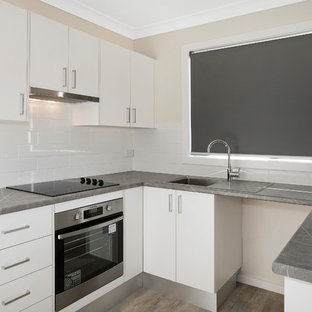 Inspiration for a small traditional u-shaped open plan kitchen in Central Coast with a single-bowl sink, louvered cabinets, laminate benchtops, white splashback, ceramic splashback, stainless steel appliances, vinyl floors, no island and brown floor.