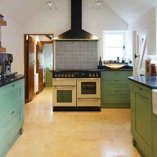 Photo of a classic u-shaped kitchen in Other with a belfast sink, shaker cabinets, green cabinets, grey splashback, white appliances, beige floors and black worktops.