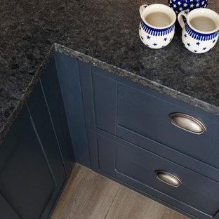 ケントの中サイズのラスティックスタイルのおしゃれなキッチン (ダブルシンク、シェーカースタイル扉のキャビネット、青いキャビネット、御影石カウンター、グレーのキッチンパネル、石スラブのキッチンパネル、黒い調理設備、クッションフロア) の写真
