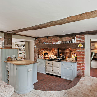 This is an example of a farmhouse l-shaped open plan kitchen in London with a double-bowl sink, recessed-panel cabinets, blue cabinets, granite worktops, red splashback, brick splashback, white appliances, brick flooring, an island and red floors.