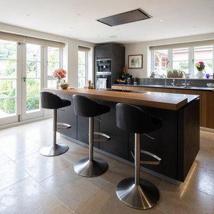 Große Klassische Wohnküche in L-Form mit integriertem Waschbecken, flächenbündigen Schrankfronten, dunklen Holzschränken, Edelstahl-Arbeitsplatte, Küchenrückwand in Grau, Rückwand aus Steinfliesen, Küchengeräten aus Edelstahl, Kalkstein, Kücheninsel, rosa Boden und grauer Arbeitsplatte in Hampshire