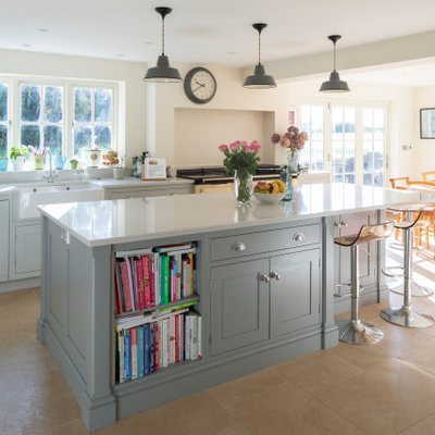 Inspiration for a mid-sized timeless u-shaped limestone floor and beige floor eat-in kitchen remodel in Hampshire with shaker cabinets, gray cabinets, granite countertops, white backsplash, stone slab backsplash, an island, white countertops and a farmhouse sink