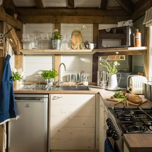 Small rustic l-shaped open plan kitchen in Sussex with a built-in sink, shaker cabinets, white cabinets, wood worktops, white splashback, wood splashback, stainless steel appliances, light hardwood flooring and beige floors.