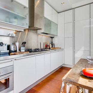 ロンドンの小さいエクレクティックスタイルのおしゃれなキッチン (フラットパネル扉のキャビネット、白いキャビネット、ステンレスカウンター、メタリックのキッチンパネル、メタルタイルのキッチンパネル、シルバーの調理設備の、無垢フローリング、アイランドなし、茶色い床、グレーのキッチンカウンター) の写真