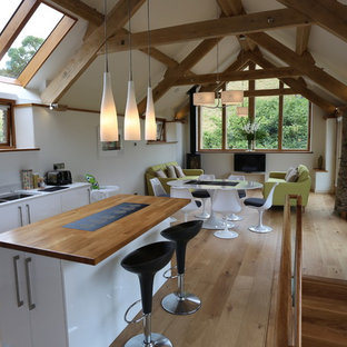 Design ideas for a small contemporary u-shaped open plan kitchen in Devon with a submerged sink, flat-panel cabinets, white cabinets, wood worktops, white splashback, stone tiled splashback, stainless steel appliances, medium hardwood flooring and an island.