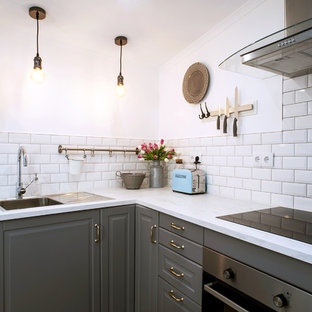 Design ideas for a small vintage l-shaped kitchen/diner in Other with a single-bowl sink, raised-panel cabinets, white cabinets, wood worktops, white splashback, metro tiled splashback, stainless steel appliances, ceramic flooring, no island and beige floors.