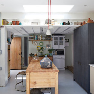Design ideas for a medium sized farmhouse single-wall kitchen in Hertfordshire with a submerged sink, flat-panel cabinets, blue cabinets, white splashback, an island, grey floors and white worktops.