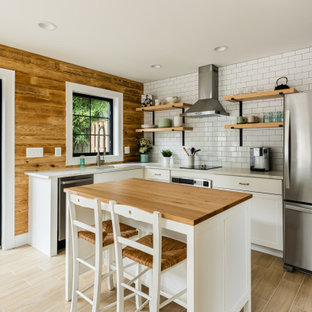 Design ideas for a mid-sized country l-shaped kitchen in DC Metro with shaker cabinets, white cabinets, wood benchtops, white splashback, subway tile splashback, stainless steel appliances, with island, brown benchtop, an undermount sink and beige floor.