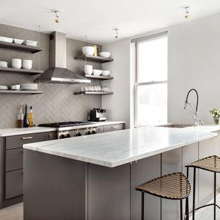 Offene, Zweizeilige, Kleine Moderne Küche mit Unterbauwaschbecken, flächenbündigen Schrankfronten, grauen Schränken, Küchenrückwand in Grau, Rückwand aus Metrofliesen, Küchengeräten aus Edelstahl, hellem Holzboden und Halbinsel in New York