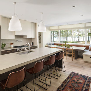 Contemporary eat-in kitchen appliance - Trendy light wood floor and beige floor eat-in kitchen photo in Portland Maine with an undermount sink, flat-panel cabinets, beige cabinets, beige backsplash, stainless steel appliances, an island and concrete countertops