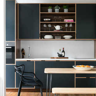 Contemporary single-wall kitchen in London with flat-panel cabinets, blue cabinets, composite countertops, white splashback, integrated appliances and medium hardwood flooring.