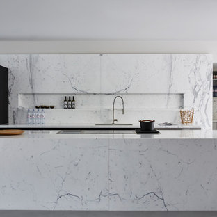 Photo of a medium sized contemporary galley kitchen in London with a submerged sink, flat-panel cabinets, white cabinets, marble worktops, an island, grey floors, grey splashback, marble splashback, black appliances and concrete flooring.
