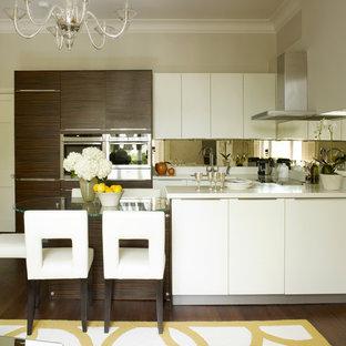 Idéer för ett litet modernt kök, med en undermonterad diskho, släta luckor, vita skåp, bänkskiva i kvarts, stänkskydd med metallisk yta, spegel som stänkskydd, rostfria vitvaror och en köksö