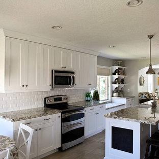 ソルトレイクシティの中サイズのエクレクティックスタイルのおしゃれなキッチン (エプロンフロントシンク、シェーカースタイル扉のキャビネット、白いキャビネット、御影石カウンター、白いキッチンパネル、セラミックタイルのキッチンパネル、シルバーの調理設備の、セラミックタイルの床) の写真