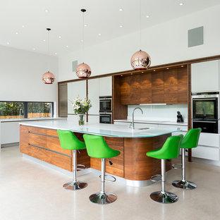 Inspiration pour une cuisine design avec un évier encastré, un placard à porte plane, des portes de placard blanches, une crédence blanche, un électroménager noir et un îlot central.