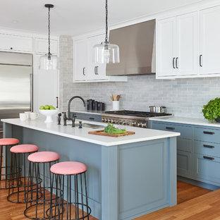 Ejemplo de cocina clásica renovada con fregadero bajoencimera, puertas de armario azules, salpicadero verde, salpicadero de azulejos tipo metro, electrodomésticos de acero inoxidable, suelo de madera en tonos medios, una isla, suelo naranja y encimeras blancas