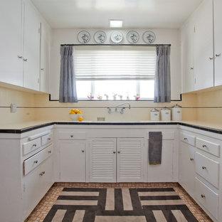Inredning av ett klassiskt avskilt, mellanstort kök, med släta luckor, vita skåp, kaklad bänkskiva, gult stänkskydd, en undermonterad diskho och rostfria vitvaror