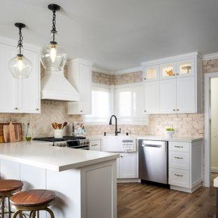 Idéer för ett mellanstort klassiskt beige kök, med en rustik diskho, skåp i shakerstil, vita skåp, bänkskiva i koppar, beige stänkskydd, stänkskydd i tegel, rostfria vitvaror, mellanmörkt trägolv, en halv köksö och brunt golv