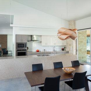 Idée de décoration pour une cuisine américaine vintage avec un évier encastré, un placard à porte plane, des portes de placard grises, une crédence blanche, une crédence en feuille de verre, un électroménager en acier inoxydable, béton au sol, un îlot central, un sol gris et un plan de travail gris.