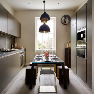 This is an example of a medium sized contemporary galley kitchen/diner in Essex with a submerged sink, flat-panel cabinets, grey cabinets, grey splashback, integrated appliances, medium hardwood flooring and no island.