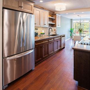 ニューヨークの中サイズのトランジショナルスタイルのおしゃれなキッチン (アンダーカウンターシンク、シェーカースタイル扉のキャビネット、濃色木目調キャビネット、ラミネートカウンター、マルチカラーのキッチンパネル、レンガのキッチンパネル、シルバーの調理設備の、クッションフロア、茶色い床、グレーのキッチンカウンター) の写真