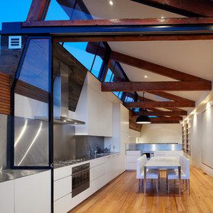 Industrial Wohnküche in L-Form mit flächenbündigen Schrankfronten, weißen Schränken, Edelstahl-Arbeitsplatte, Küchenrückwand in Metallic, Einbauwaschbecken, Rückwand aus Metallfliesen, Küchengeräten aus Edelstahl und hellem Holzboden in Melbourne