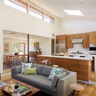 Esempio di una cucina ad ambiente unico minimalista di medie dimensioni con ante lisce, ante in legno scuro, elettrodomestici in acciaio inossidabile, parquet chiaro, isola e top bianco