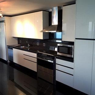 シカゴの広いモダンスタイルのおしゃれなキッチン (アンダーカウンターシンク、フラットパネル扉のキャビネット、白いキャビネット、ラミネートカウンター、黒いキッチンパネル、セラミックタイルのキッチンパネル、シルバーの調理設備、セラミックタイルの床、アイランドなし) の写真