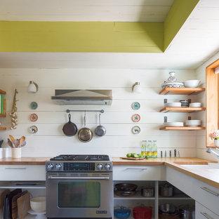 オースティンの小さいエクレクティックスタイルのおしゃれなキッチン (アンダーカウンターシンク、フラットパネル扉のキャビネット、白いキャビネット、木材カウンター、木材のキッチンパネル、アイランドなし、白いキッチンパネル、シルバーの調理設備の、ベージュのキッチンカウンター) の写真