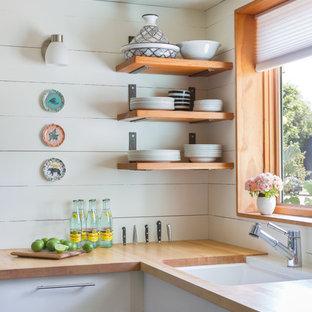 オースティンの小さいエクレクティックスタイルのおしゃれなキッチン (アンダーカウンターシンク、フラットパネル扉のキャビネット、白いキャビネット、木材カウンター、木材のキッチンパネル、アイランドなし) の写真