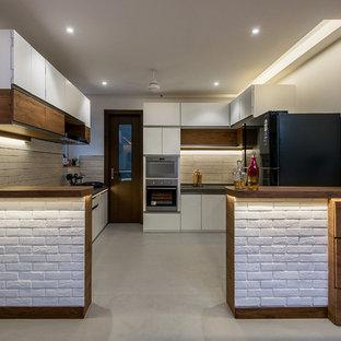 Ejemplo de cocina ecléctica con armarios con paneles lisos, suelo gris, puertas de armario blancas, salpicadero blanco, electrodomésticos negros y península