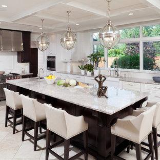 ニューヨークの広い地中海スタイルのおしゃれなアイランドキッチン (エプロンフロントシンク、レイズドパネル扉のキャビネット、白いキャビネット、御影石カウンター、白いキッチンパネル、シルバーの調理設備、ライムストーンの床、ベージュの床、セラミックタイルのキッチンパネル、ベージュのキッチンカウンター) の写真