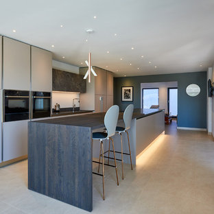 Large contemporary single-wall open plan kitchen in West Midlands with a built-in sink, flat-panel cabinets, grey cabinets, granite worktops, black appliances, limestone flooring, an island, beige floors and grey worktops.
