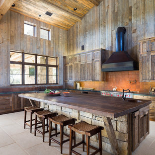 Rustic open concept kitchen designs - Example of a mountain style l-shaped open concept kitchen design in Austin with shaker cabinets, medium tone wood cabinets, wood countertops, orange backsplash, terra-cotta backsplash and stainless steel appliances