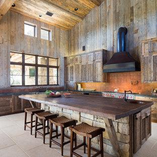 オースティンのラスティックスタイルのおしゃれなキッチン (シェーカースタイル扉のキャビネット、中間色木目調キャビネット、木材カウンター、オレンジのキッチンパネル、テラコッタタイルのキッチンパネル、シルバーの調理設備) の写真