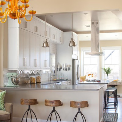Transitional u-shaped open concept kitchen photo in Denver with a farmhouse sink, recessed-panel cabinets, white cabinets, white backsplash, subway tile backsplash and stainless steel appliances