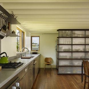 Idéer för att renovera ett mellanstort funkis kök, med rostfria vitvaror, en undermonterad diskho, släta luckor, skåp i mellenmörkt trä, bänkskiva i rostfritt stål, stänkskydd med metallisk yta och mellanmörkt trägolv