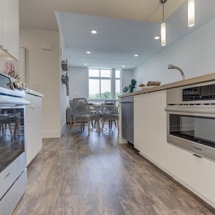 Open concept kitchen inspiration - Example of a l-shaped light wood floor open concept kitchen design in San Francisco with flat-panel cabinets, white cabinets, white backsplash, stainless steel appliances and an island