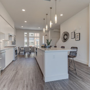 Open concept kitchen pictures - Example of a single-wall light wood floor and gray floor open concept kitchen design in San Francisco with flat-panel cabinets, white cabinets, white backsplash, stainless steel appliances and an island