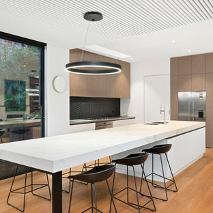 Design ideas for a contemporary u-shaped kitchen in Melbourne with an undermount sink, flat-panel cabinets, medium wood cabinets, black splashback, stainless steel appliances, medium hardwood floors, with island, brown floor and grey benchtop.