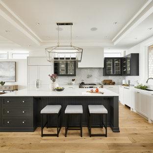 他の地域の広いトランジショナルスタイルのおしゃれなキッチン (アンダーカウンターシンク、シェーカースタイル扉のキャビネット、珪岩カウンター、白いキッチンパネル、サブウェイタイルのキッチンパネル、パネルと同色の調理設備、白いキッチンカウンター、白いキャビネット、無垢フローリング、茶色い床、折り上げ天井) の写真