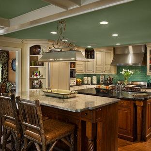 フィラデルフィアのカントリー風おしゃれなキッチン (アンダーカウンターシンク、レイズドパネル扉のキャビネット、ヴィンテージ仕上げキャビネット、ソープストーンカウンター、緑のキッチンパネル、サブウェイタイルのキッチンパネル、シルバーの調理設備の、淡色無垢フローリング) の写真
