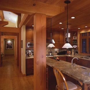 シアトルの中サイズのトラディショナルスタイルのおしゃれなキッチン (アンダーカウンターシンク、落し込みパネル扉のキャビネット、中間色木目調キャビネット、御影石カウンター、マルチカラーのキッチンパネル、スレートのキッチンパネル、シルバーの調理設備、無垢フローリング、茶色い床、茶色いキッチンカウンター) の写真