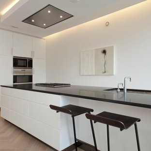 This is an example of a contemporary kitchen in Amsterdam with flat-panel cabinets, white cabinets and black benchtop.