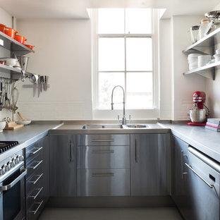 Bild på ett avskilt, mellanstort skandinaviskt u-kök, med en integrerad diskho, släta luckor, skåp i rostfritt stål, bänkskiva i rostfritt stål, vitt stänkskydd, stänkskydd i keramik, rostfria vitvaror och målat trägolv