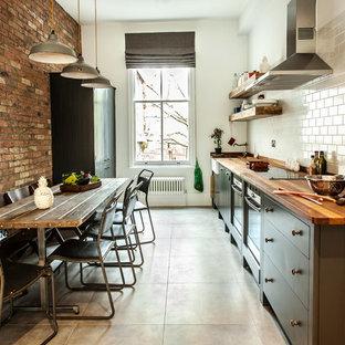 Inspiration för ett avskilt, mellanstort industriellt linjärt kök, med träbänkskiva, vitt stänkskydd och stänkskydd i tunnelbanekakel