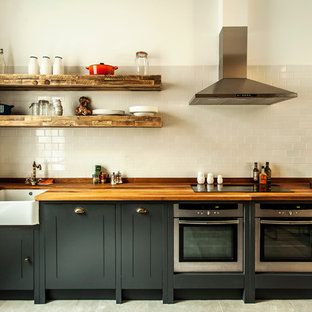 Inspiration for an industrial kitchen in London with wood worktops.