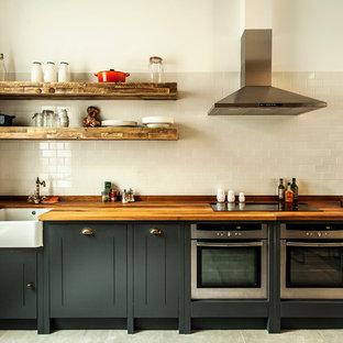 Exemple d'une cuisine industrielle avec un plan de travail en bois.