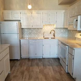 Geschlossene, Mittelgroße Küche ohne Insel in L-Form mit Unterbauwaschbecken, profilierten Schrankfronten, weißen Schränken, Arbeitsplatte aus Terrazzo, Küchenrückwand in Weiß, Rückwand aus Keramikfliesen, weißen Elektrogeräten und hellem Holzboden in Bridgeport